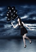 Fashion photoshoot with  a beautiful young woman flying with balloons