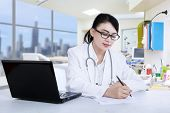 image of prescription  - Attractive female doctor is writing prescription at the clinic - JPG