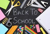 The words Back to School written on a chalkboard surrounded by school supplies including, paper, sc