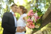 Wedding shot of bride and groom stand in park (focus on bouquet)