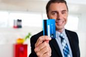 picture of plastic money  - Businessman in formals holding up his credit card and showing to the camera - JPG