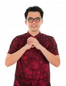 Asian man with Chinese traditional dress cheongsam or tang suit greeting. Chinese new year concept, male model isolated on white background.