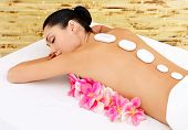 Woman At Spa Salon. White ?ot Stones On Female Back.
