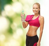 fitness, health and diet concept - sporty woman with bottle of water and towel