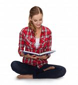 education and leisure concept - smiling young woman sittin on floor with book
