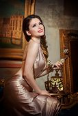Young beautiful luxurious woman in elegant dress smiling holding a vintage telephone