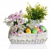 colorful easter eggs with pink flowers in basket isolated on white background