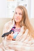 Bored young woman covered with blanket holding cup and remote control and watching tv at home