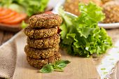pic of veggie burger  - Vegan burgers with lentils and pistachios stacked on a cutting board - JPG