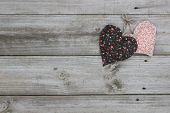 foto of wood craft  - Brown and peach calico hearts hanging on wooden background - JPG