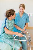 Happy mid adult nurse assisting female patient using walker in hospital