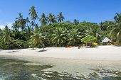 A look at a Fijian tropical resort from the water showing its lush surroundings and recreational kay