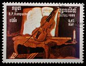 Kampuchea-CIRCA 1985: A stamp printed in the Kampuchea, depicts a violin lying on an armchair, circa 1985