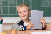 picture of peer  - Cute laughing little boy using a tablet in school peering around the side to give the camera a big cheerful grin