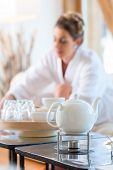 Woman in bath robe drinking tea in wellness spa relaxation room