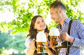 German couple in Tracht drinking beer in the shadow of trees