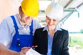 Team or architect and builder or worker with helmets controlling or discuss  construction plan or bl