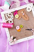 Scrapbooking craft materials and wooden frame with sackcloth inside on color wooden background