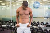 Determined young shirtless man lifting barbell in gym