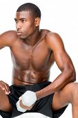 Determined fit shirtless young man lifting dumbbell over white background