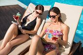 Two beautiful young women with drinks reading books by swimming pool