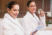 Young women in bathrobes drinking water and text messaging on couch