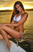 Model wearing white stylish swimwear and posing on deck of motorboat