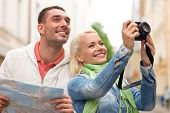 travel, vacation, technology and friendship concept - smiling couple with map and photocamera explor