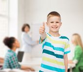 childhood, school, education and people concept - smiling little boy showing thumbs up over group of