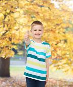 happiness, childhood, seasons and people concept - smiling little boy in casual clothes showing thum