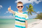 childhood, travel, summer vacation, gesture and people concept - smiling little boy wearing sunglass