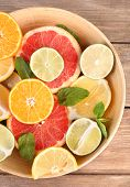 Different sliced juicy citrus fruits in bowl on wooden table