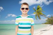 childhood, summer, travel, vacation and people concept - smiling little boy wearing sunglasses over