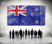 Silhouettes of Business People Looking at the Flag of New Zealand