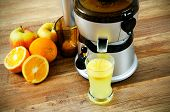 Juicer And Orange Juice On Wooden Background