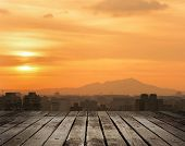 Sunset cityscape with dramatic clouds in orange and yellow color in Taipei, Taiwan, Asia. Focus on wooden floor.
