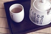 A Mug With Hot Green Tea And A Teapot On The Tray