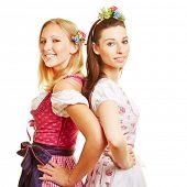 Two happy women in dirndl dress smiling at Oktoberfest