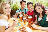 Happy group of people drinking beer together in garden in summer