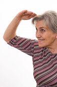 Smiling Senior Woman Shielding Her Eyes Isolated On White