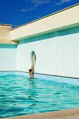 child climbs on the edge of the pool, outdoor