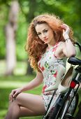 Beautiful girl wearing a nice short dress having fun in park with bicycle. Pretty long hair woman