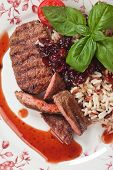 Grilled steak, medium done, with rice and cranberry sauce