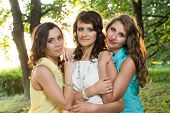 Three young beautiful ladies posing during walk in the city park near bank of the river