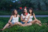Three happy girlfriend on a picnic in short shorts and white T-shirts sit on the grass