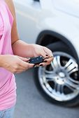 Unrecognizable Caucasian Woman With Ignition Key Standing Near New Car