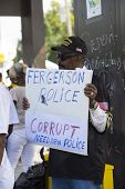 FERGUSON, MO/USA  AUGUST 15, 2014: Demonstrator holds sign at the site of destroyed Quick Trip after