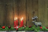 Four Red Burning Christmas Candles On Wood Background With Deer.