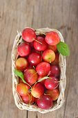 cherry-plum in basket on wooden background