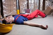 picture of workplace accident  - Unconscious warehouse worker after falling from a ladder